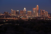 The violet crown sunset falls on the downtown Austin skyline as wintertime violet glow of color paints the skyscrapers across the hills from Rollingwood Westalke area of town