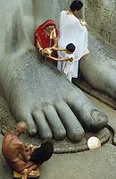 INDIEN Karnataka, Jain Glaeubige und nackter Moench beim Gebet am Jainheiligtum Bahubali eine 17 Meter hohe Statue aus Granit des Jain Heiligen Lord Bahubali oder Gommata oder Gomateshvara in Shravana Belagola , Jains praktizieren als oberstes Gebot Gewaltverzicht ahimsa und sind strikte Vegetarier und lehnen das Kastensystem ab - Religion Jainismus als Reformbewegung aus Hinduismus hervorgegangen / INDIA Shravana Belagola Karnataka , pilgrims and naked Jain monk at Jain statue Bahubali