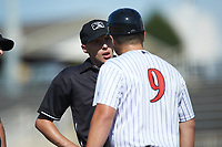 Home plate umpire Matt Baldwin listens as Kannapolis Intimidators manager Justin Jirschele (9) argues a call that was reversed during the game against the Greensboro Grasshoppers at Kannapolis Intimidators Stadium on August 5, 2018 in Kannapolis, North Carolina. The Intimidators defeated the Grasshoppers 9-0 in game two of a double-header.  (Brian Westerholt/Four Seam Images)