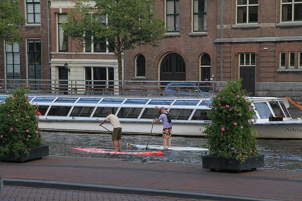 Standup kayak paddlers on the Spaarne River in Haarlem, Holland, Netherlands.
