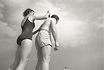 Woman putting suntan lotion on senior man. 1978. Brigantine Beach, New Jersey