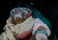 """The bodies of a Palestinian mother (top-L) and her four children lie in the morgue of a hospital prior to their funeral in Beit Lahia in the northern Gaza Strip on April 28, 2008. Four children, aged one to five, their mother and a militant were killed in Israeli operations in Gaza today as Palestinian factions headed to Egypt for talks on a possible truce. The four siblings -- aged one, three, four and five -- were killed when a tank shell hit their home in the town of Beit Hanun, and their mother died later of her wounds, doctors at the Kamal Radwan hospital said.""""photo by Fady Adwan"""""""