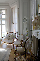 A pair of gilded Gustavian armchairs and a matching sofa next to the Mora clock in the living room