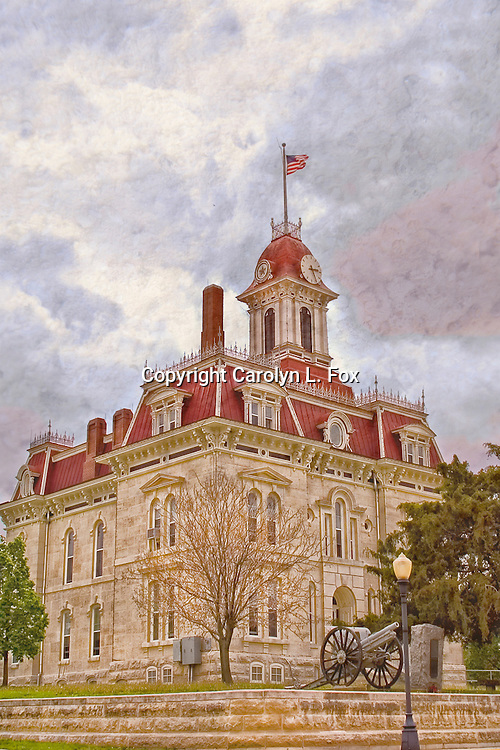 An old, historic courthouse stands under a cloudy sky in the mid-west.