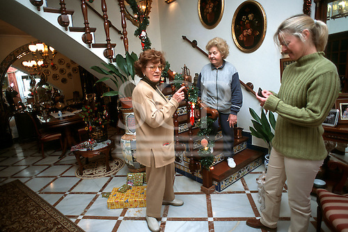 Seville, Spain. Two middle-aged women with the grandmother of one of them in the hall of their affluent apartment at Christmas.