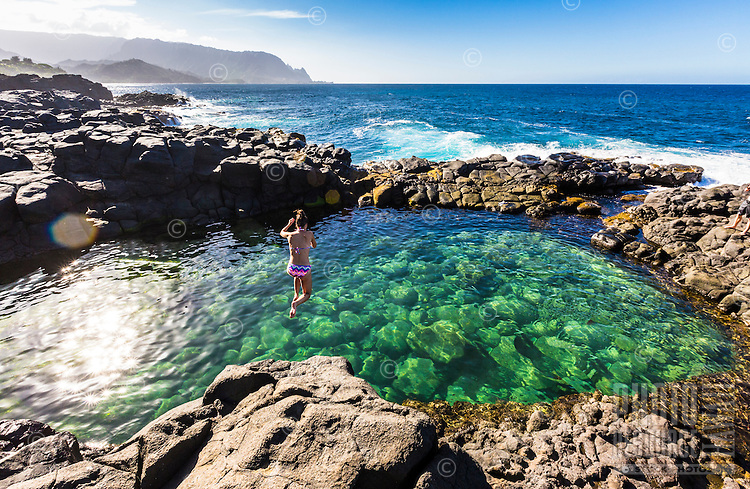 A young woman jumps into the crystal clear water of Queen's Bath, Princeville, North Shore of Kaua'i. A sacred place where visitors must be very careful of the incoming surf!