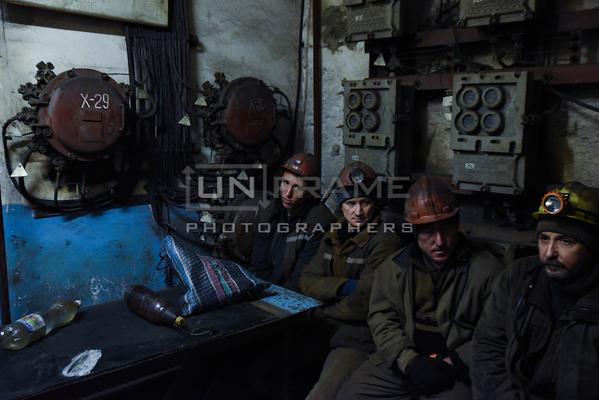 Ukrainian coal miners wait in a room before going underground to help search for bodies of colleagues and clear up debris following an explosion at the Zasyadko mine in Donetsk, Ukraine, Wednesday, March 4, 2015