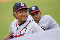 Yeliar Castro #45 of the Rome Braves smiles as he watches the Kannapolis Intimidators mascot dance on their dugout between innings at Fieldcrest Cannon Stadium July 28, 2009 in Kannapolis, North Carolina. (Photo by Brian Westerholt / Four Seam Images)