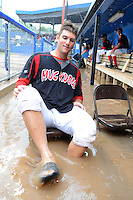 Batavia Muckdogs starting pitcher Trevor Williams (46) takes a seat after the dugout flooded during a brief but heavy rain storm during a game against the Hudson Valley Renegades on August 8, 2013 at Dwyer Stadium in Batavia, New York.   The game was called due to unplayable field conditions.  (Mike Janes/Four Seam Images)