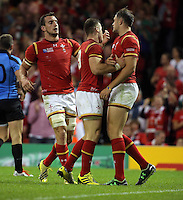 Pictured: Cory Allen of Wales (R) celebrates his try with team mates L-R Sam Warburton and Gareth Davies  just before the end of the first half Sunday 20 September 2015<br />Re: Rugby World Cup 2015, Wales v Uruguay at the Millennium, Stadium, Wales, UK