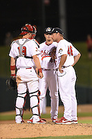 Peoria Chiefs pitching coach Jason Simontacchi (46) talks with catcher Carson Kelly (19) and pitcher Brandon Lee (40) during a game against the Kane County Cougars on June 2, 2014 at Dozer Park in Peoria, Illinois.  Peoria defeated Kane County 5-3.  (Mike Janes/Four Seam Images)