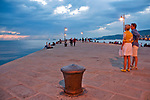 A couple on Molo Audace pier at sunset, looking at the Gulf of Trieste, Italy