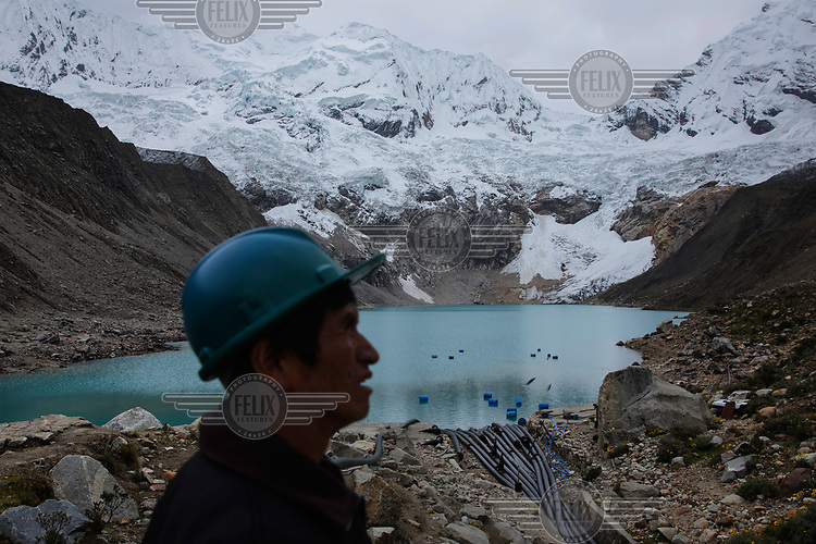 Juan Victor Morales Moreno (52) looks down at pipes that drain Lake Palcacocha in the Cordillera Blanca. His job is to watch the lagoon 24 hours a day and report by radio any disturbance to the Regional Operations and Emergency Center in nearby Huaraz. Due to the increased volume of water, originating from melting glaciers around the lake, avalanches have the potential to create massive waves, generating mudslides that could be devastating for the nearby city of Huaraz, as happened in 1941, when 2,000 people died.