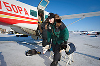 Laura Dagereau, who scratched in in Grayling, takes her dogs out of the Penair Caravan plane in Unalakleet during Iditarod 2009