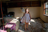 Haley Verdin in her living room after hurricanes Gustav and Ike tore through the Native American community of Point Aux Chene, Louisiana damaging the roof of her family's house. Point Aux Chene, is among the dozen or so small towns on the brink of collapse due to coastal erosion, as the Gulf of Mexico creeps further inland.
