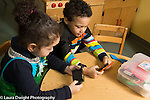 Education Preschool 3 year olds boy and girl pretend play with cell telephones sitting side by side