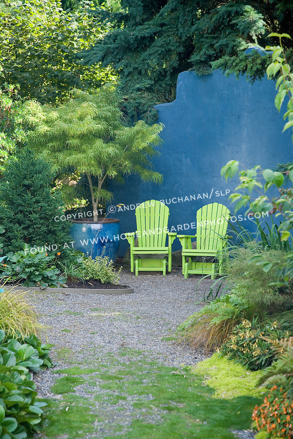 A gravel path at the back of a residential organic garden north of Seattle leads to a gravelled sitting area furnished with two chartreuse green Adirondack chairs and backed by a roughly 9 foot tall blue wall, reminiscent of a Caribbean patio, that provides color at the back of the garden as well as privacy from a storage area behind.