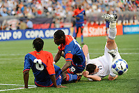 Kenny Cooper (17) of the United States (USA) goes down n a collision with Judelin Aveska (8) and Pierre Bruny (13) of Haiti (HAI). The United States and Haiti played to a 2-2 tie during a CONCACAF Gold Cup Group B group stage match at Gillette Stadium in Foxborough, MA, on July 11, 2009. .