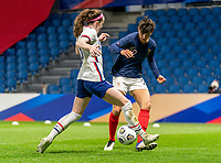 LE HAVRE, FRANCE - APRIL 13: Rose Lavelle #16 of the USWNT tackles the ball away from Elisa De Almeida #22 of France during a game between France and USWNT at Stade Oceane on April 13, 2021 in Le Havre, France.