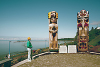 White Rock, BC, British Columbia, Canada - Coast Salish and Haida Totem Poles in Lions Park, along Seaside Promenade Walkway and Semiahmoo Bay (Model Released Person in foreground)