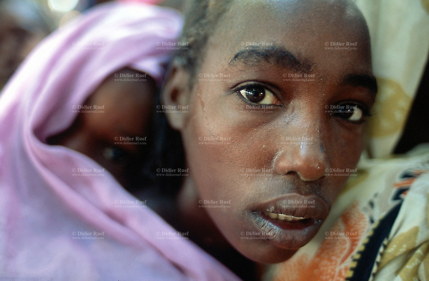 Sudan. West Darfur. Kerenek. The non-governmental organization (ngo) Médecins sans Frontières (MSF) Switzerland distributes food and oil to mothers whose children have a height below one meter and 10.  A girl carrying her yougest sister on her back waits on line. © 2004 Didier Ruef