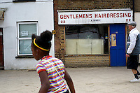 People walk past the damaged window of a hairdressing salon in Tottenham, London borough of Haringey. London saw the beginnings of riots on Saturday evening, after a peaceful protest in response to the shooting by police of Mark Duggan during an attempted arrest, escalated into violence. By the third night of violence, rioting had spread to many areas of the capital and to other cities around the country.