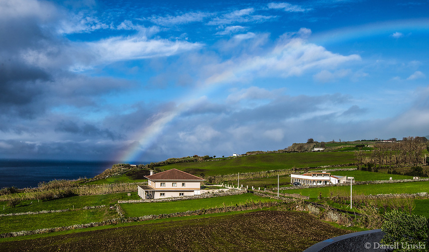 Fine Art Landscape Photograph of a rainbow spreading it's arch over the countryside of Ponta Delgada.