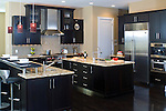 A contemporary kitchen featuring cherry cabinets with a dark coffee color finish.