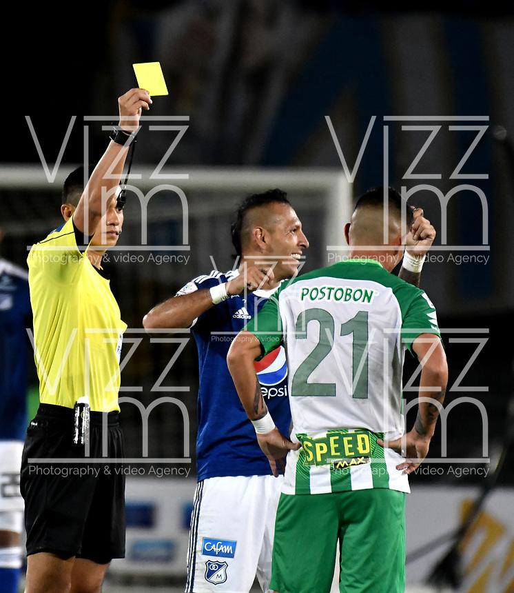 BOGOTA - COLOMBIA - 18 – 02 - 2018: Carlos Mario Herrera (Izq.), arbitro, muestra tarjeta amarilla a Jorman Campuzano (Der.) jugador de Millonarios, durante partido de la fecha 4 entre Millonarios y Atletico Nacional, por la Liga Aguila I 2018, jugado en el estadio Nemesio Camacho El Campin de la ciudad de Bogota. / Carlos Mario Herrera (L), referee, shows yellow card to Jorman Campuzano (R), player of Millonarios during a match of the 4th date between Millonarios and Atletico Nacional, for the Liga Aguila I 2018 played at the Nemesio Camacho El Campin Stadium in Bogota city, Photo: VizzorImage / Luis Ramirez / Staff.