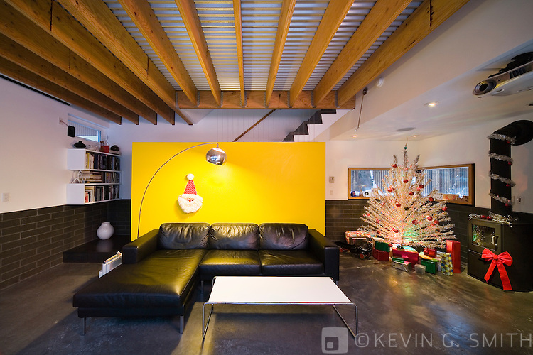 Living room in a modern style home decorated for christmas, 60's retro aluminum Christmas tree, wood stove.
