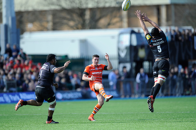Freddie Burns of Leicester Tigers chips past Alistair Hargreaves and Mako Vunipola of Saracens during the Aviva Premiership Rugby match between Saracens and Leicester Tigers at Allianz Park on Saturday 11th April 2015 (Photo by Rob Munro)