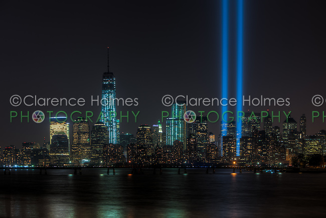 The twin beams of light of the Tribute in Light, an annual memorial to the events of September 11, 2001, shine into the evening sky in New York City over the skyline of lower Manhattan on Wednesday, September 11, 2013.  This view of the skyline includes the Freedom Tower (One World Trade Center), under construction at the site of the original Twin Towers.