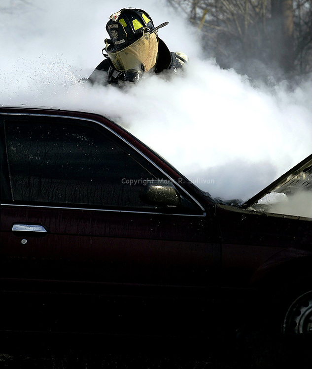 (FIRE)--28856-On Sun Jan 19,2003-carfire0119B--A firefighter from the East Brunswick Independent Fire Company emergers from the smoke & steam as he works  a car on fire on the jughandle to Edgeboro Rd right off of RT 18 South in East Brunswick. The car caught fire after the driver smelled an odor of gas , then the car stalled. No one was hurt in the fire and was qucikly brought under control. The jughandle was closed to traffic for an hour while the clean up took place. (MARK R. SULLIVAN/HNT CHIEF PHOTOGRAPHER)