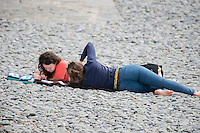 Aberystwyth Wales UK, Friday 06 May 2016<br /> UK Weather:  Two young women students revising  on the beach on a bright, warm, but overcast day in Aberystwyth Wales.<br /> The Met Office have issued an amber warning for heavy rainstorms over the whole of Wales at times tomorrow (saturday) as the temperature climbs to the mid 20's centigrade