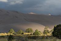 A ray of sunlight illuminates parts of the dunes.