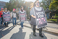 """Protestors march along Tremont Street as they make their way to Boston City Hall during the 2020 Women's March protest in opposition to the re-election of US president Donald Trump in Boston, Massachusetts, on Sat., Oct. 17, 2020.<br /> The signs here resemble the robe and lace dissent collar of recently-deceased Supreme Court Justice and read """"Vote for Truth!"""" """"Fight for things you care about,"""" and """"Women belong in all places where decisions are being made."""""""