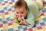 5 month old baby boy on stomach, closeup, biting toy he holds