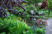 Garden room outdoor seating, chairs by pond in O'Byrne Garden
