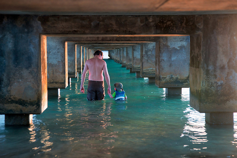 Father and son walking under warf at Hanalei Bay, Kauai, Hawaii.