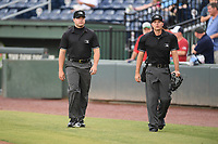 First base umpire Colin Baron, left, and home plate umpire Adam Clark get ready to work a game between the Greenville Drive and the Asheville Tourists on Friday, August 23, 2019, at Fluor Field at the West End in Greenville, South Carolina. Greenville won, 11-1. (Tom Priddy/Four Seam Images)