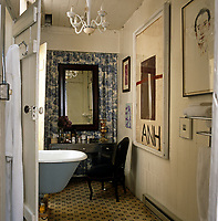 The small bathroom has a chrome dressing table and roll-top bath and is decorated with a painting by Julian Schnabel and a Murano glass chandelier