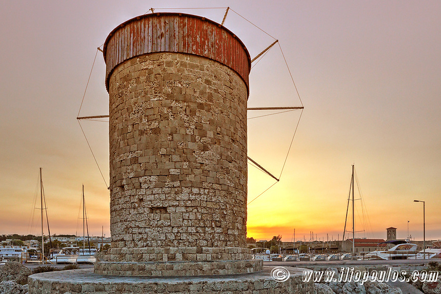 The sunset at a windmill of the old port of Rhodes, Greece