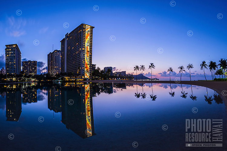 The Hilton's Rainbow Tower in Waikiki just before sunrise, with Diamond Head in the distance, Honolulu, O'ahu.