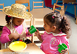 Education preschool 3-4 year olds pretend play girls in dressup clothes playing game with toy dishes and bags horizontal