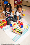 Education preschool 3-4 year olds two girls playing together in family area setting out picnic on blanket with toy foods vertical