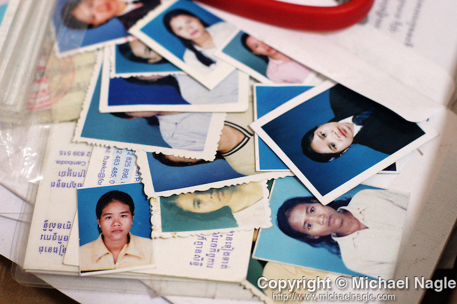 CAMBODIA -- APRIL 11, 2005:   Photos of Cambodian textile workers ready to be made into identification cards at their union office in Phnom Penh on April, 11 2005 in Cambodia. Thanks to an unorthodox labor program backed by the United States and intended to improve working conditions, much of Cambodia's garment industry has been holding its own since the end of the global quota system that parceled out shares of the apparel and textile business country by country. A majority of Cambodia's factories have retained the loyalty of major retailers around the world by appealing not just to their need for low-cost production but also to their desire to avoid the stigma of exploiting poor laborers in distant sweatshops. (PHOTOGRAPH BY MICHAEL NAGLE)