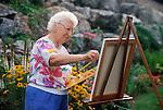 elderly woman painting landscape in garden