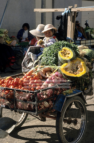 Juliaca, Peru. Rural Indians with their produce - tomatoes, onions, carrots, potatoes, pumpkins at market.