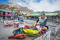 A woman sits at a guesthouse in Chukhung, Nepal, organizing her gear for a trail run and fast packing trip through the Khumbu Valley.