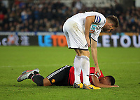 Anthony Martial of Manchester United lies on the ground in agony after a challenge by Angel Rangel of Swansea City who checks that he is all right during the Carabao Cup Fourth Round match between Swansea City and Manchester United at The Liberty Stadium, Swansea, Wales, UK. Tuesday 24 October 2017